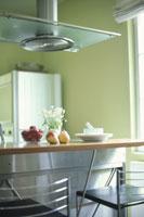 カウンターの上のイチゴや洋ナシと黄緑の壁のキッチン
