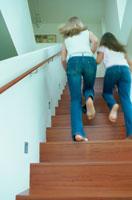 素足で階段をかけ上る母と娘