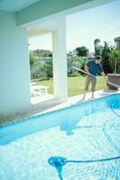プールを掃除する男性