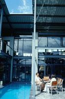 プールサイドのイスで話すカップル 21022002641| 写真素材・ストックフォト・画像・イラスト素材|アマナイメージズ