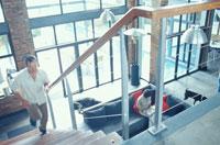階段を上る男性とソファで本を読む女性と犬 21022002655| 写真素材・ストックフォト・画像・イラスト素材|アマナイメージズ