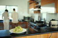 キッチンカウンターの上の洋梨と後姿のカップル