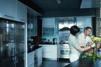 キッチンで花を生けるカップル