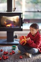 リビングでプレゼントを開けようとする女の子 21022002779| 写真素材・ストックフォト・画像・イラスト素材|アマナイメージズ