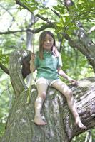 木に座る女の子 21022002800A| 写真素材・ストックフォト・画像・イラスト素材|アマナイメージズ