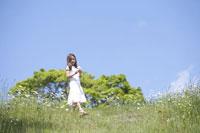 草原を歩く女の子 21022002804D| 写真素材・ストックフォト・画像・イラスト素材|アマナイメージズ