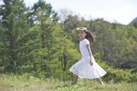 草原を歩く女の子 21022002811| 写真素材・ストックフォト・画像・イラスト素材|アマナイメージズ