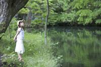 池の畔に立つ女の子 21022002818A| 写真素材・ストックフォト・画像・イラスト素材|アマナイメージズ