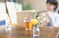テーブルの上の花瓶と飲み物 奥に日本人女性
