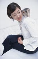 女性の肩に乗った猫(アビシニアン)