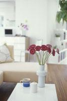 花瓶に生けた赤いガーベラのある室内