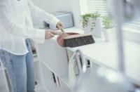キャビネットの上を掃除する女性の手元