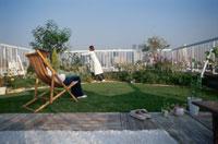 屋上の庭の手入れをする女性