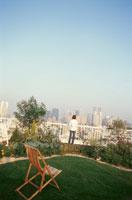 屋上の庭から街を眺める女性