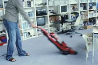 赤い掃除機で部屋を掃除する男性