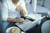 ベーグルをのせたデスクでノートパソコンを使う男性