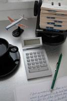 デスクの上の計算機やコーヒーや名刺ホルダー
