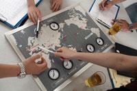 世界時計を見ながらミーティングをする人の手元