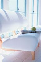 白いソファに英字新聞と青リンゴ