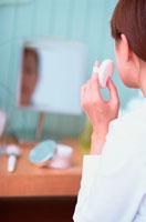 鏡に向かって化粧をする女性