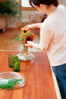 花瓶にひまわりを生ける女性