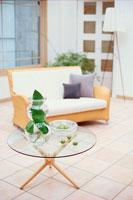 ガラスの丸テーブルと籐のソファ