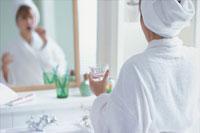 鏡に向かって歯を磨く女性