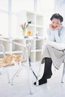 イスの上の猫を見る頬杖をつく女性