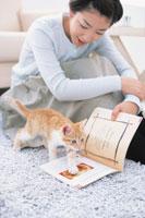 雑誌の上を歩く猫を見る女性