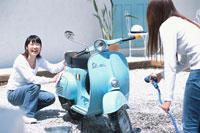 庭で水色のベスパを洗う女性2人