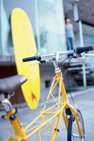 黄色い自転車越しのサーフボード