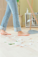 ゴミをホウキで掃き集める人の足元