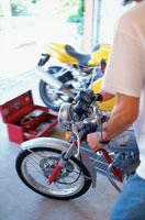 オートバイをガレージから出す男性