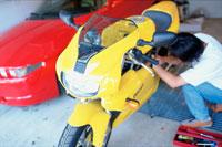 黄色いオートバイを整備する男性