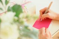 カードにメッセージを書く手元とギフト