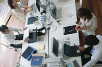 オフィスのデスクで働く男女4人 俯瞰