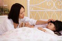 子供の熱を測る母親