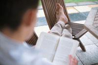 イスに足を置いて本を読む男性後姿