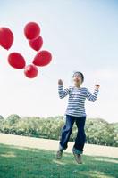赤い風船を持って飛ぶ女の子