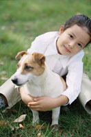 芝生に座っている犬と少女