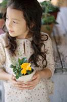 黄色い花の鉢を持ったハーフの少女