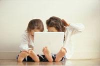 ノートパソコンを覗き込む2人の女の子