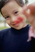 赤い物を差し出す笑顔の少女