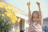 腕を伸ばす少女と黄色い花