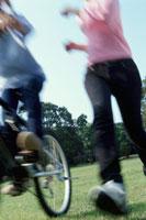 公園を走る女性と自転車で走る人