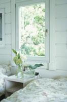 ベッドと窓際のサイドテーブルに置かれたライトと花
