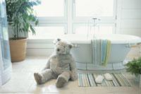 タオルをかけたバスタブとヌイグルミのあるバスルーム