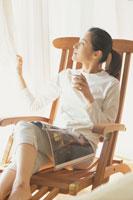 木の椅子で寛ぐ女性