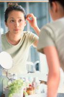 鏡に向かって身支度をする女性