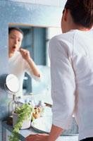 鏡に向かって歯を磨く女性 21044000843| 写真素材・ストックフォト・画像・イラスト素材|アマナイメージズ